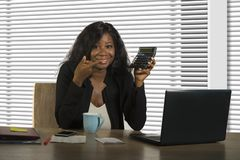 Young beautiful and confident black African American businesswoman working at office computer desk smiling holding calculator in stock photography