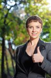 Young beautiful confident woman in formalwear happily raises her. Portrait of young beautiful confident woman in formalwear happily raises her thumb up and Stock Image