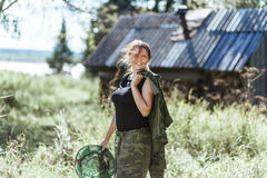 Young beautiful country woman in camouflage outfit discovering nature in the forest village with mosquito net. Travel Stock Photo