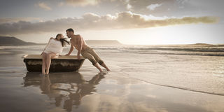 Young beautiful couple on beach at sunrise. With vintage bath tub Royalty Free Stock Photography