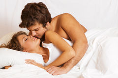 Young beautiful couple in bed Stock Photos