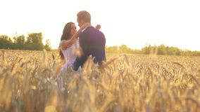 Young beautiful couple, bride and groom, go to. Each other, dancing in a wheat field, white dress and suit, romantic and tender love sunset, sunlight  1080p stock video
