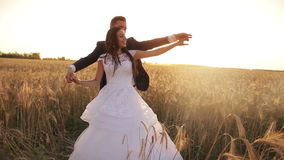 Young beautiful couple, bride and groom, go to. Young beautiful couple,  bride and groom, go to each other, dancing in a wheat field, white dress and suit stock video