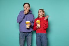 Young beautiful couple in casual clothes eating popcorn, bored during a boring movie stock images