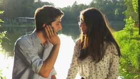 Young beautiful couple chatting and talking at the smartphone in the park stock footage