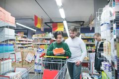 A young, beautiful couple chooses goods for a home in a supermarket. Family shopping at the store royalty free stock images