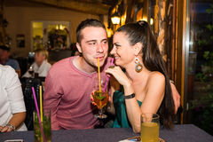 Young beautiful couple with cocktails in bar or club Stock Photography