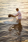 Young beautiful couple dancing in water with sunlight reflections. Beautiful couple dancing in water with sunlight reflections Stock Photo