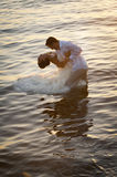 Young beautiful couple dancing in water with sunlight reflections. Beautiful couple dancing in water with sunlight reflections Stock Images