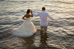 Young beautiful couple dancing in water with sunlight reflections. Beautiful couple walking into water with sunlight reflections of surface Stock Photography