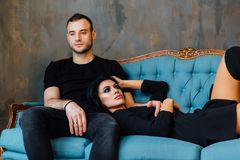 Young beautiful couple in dark clothes on a turquoise vintage couch. Studio loft. Sexy guy and girl. Have a rest on Valentine`s Day Royalty Free Stock Photo