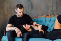 Young beautiful couple in dark clothes on a turquoise vintage couch. stock image