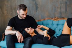 Young beautiful couple in dark clothes on a turquoise vintage couch. Studio loft. Sexy guy and girl. Have a rest on Valentine`s Day Royalty Free Stock Images
