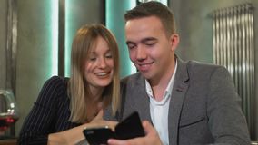A young beautiful couple on a date in a cafe watching photos on smartphone stock video