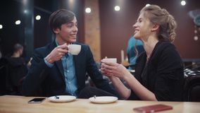 Young beautiful couple on a date talking, laughing and drinking coffee sitting in a cozy expensive restaurant. stock video footage