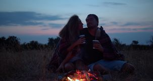 Young beautiful couple on date together near bonfire. Boyfriend and girlfriend on picnic. They kisses, hugging, love stock video footage