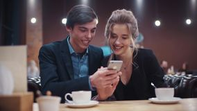 Young beautiful couple discussing cheerfully what they see on smartphone's screen and drinking coffee on a date. stock video footage