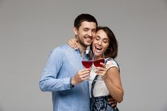 Young beautiful couple drinking wine, smiling over grey background. Royalty Free Stock Photo