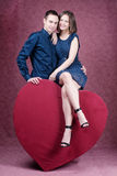 Young beautiful couple embracing in front of a huge heart Royalty Free Stock Photography