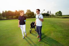 Young couple enjoying time on a golf course. Young beautiful couple enjoying time on a golf course stock photo