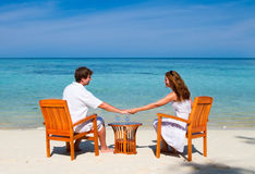 Young beautiful couple enjoying on a tropical beac. Young beautiful couple enjoying cocktails on a tropical beach stock image