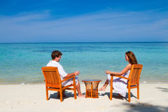 Young beautiful couple enjoying on a tropical beach. Young beautiful couple enjoying cocktails on a tropical beach Stock Photography