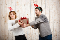 Young beautiful couple fighting for  christmas gift over wooden background. Stock Photo