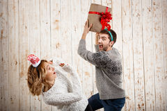 Young beautiful couple fighting for  christmas gift over wooden background. Royalty Free Stock Image
