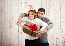 Young beautiful couple fighting for  christmas gift over wooden background. Stock Photography
