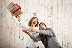 Young beautiful couple fighting for  christmas gift over wooden background. Royalty Free Stock Images