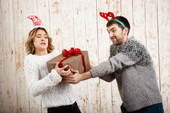 Young beautiful couple fighting for  christmas gift over wooden background. Royalty Free Stock Photo