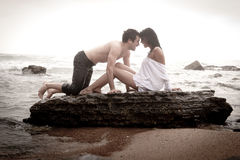 Young beautiful couple flirting at the beach. On the rocks Royalty Free Stock Photography