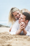Young beautiful couple flirting on beach sand Royalty Free Stock Photography