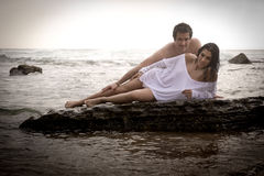 Young beautiful couple flirting at the beach. On surf rocks Royalty Free Stock Images