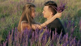 Young couple in the colors of the spring field stock footage