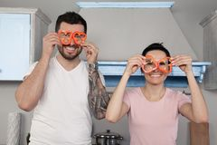 Young beautiful couple fool in the kitchen. They keep bits of Bulgarian pepper around their eyes and laugh.  stock photos