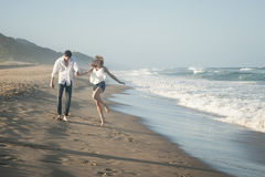 Young beautiful couple happily walking along the beach together Royalty Free Stock Images
