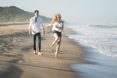 Young beautiful couple happily walking along the beach together Royalty Free Stock Photo