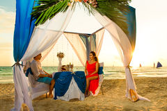 Young beautiful couple have a romantic dinner at sunset on a tropical beach . Honeymoon. royalty free stock image