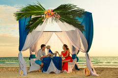 Young beautiful couple have a romantic dinner at sunset on a tropical beach . Honeymoon. royalty free stock photos