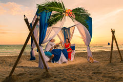Young beautiful couple have a romantic dinner at sunset on a tropical beach . Honeymoon. stock image