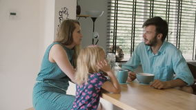 Young beautiful couple is having breakfast with their daughter in the morning. Slow motion stock video