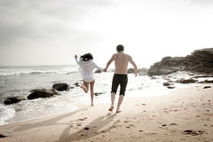 Young beautiful couple having fun jumping along beach Stock Images