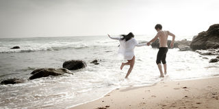 Young beautiful couple having fun jumping along beach. Sand Royalty Free Stock Images