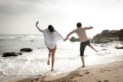 Young beautiful couple having fun jumping along beach Royalty Free Stock Image
