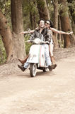 Young beautiful couple having fun with scooter. Along dirt road Royalty Free Stock Photos