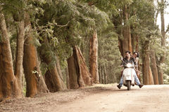 Young beautiful couple having fun with scooter. In forest Royalty Free Stock Photography
