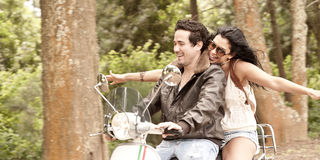 Young beautiful couple having fun with scooter. Through forest Royalty Free Stock Image
