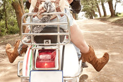 Young beautiful couple having fun with scooter Stock Image