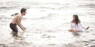 Young beautiful couple having fun in the surf. At beach Royalty Free Stock Photography